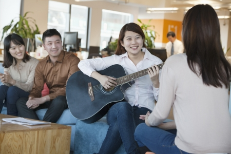 Young Office Worker Playing Guitar to Colleagues photo