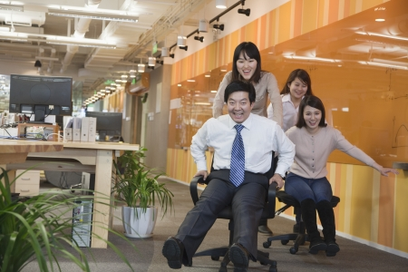 Businesswomen Pushing Her Colleagues in the Chair photo