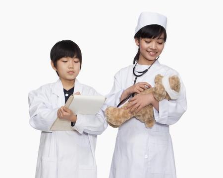 signos vitales: Niño y niña vestidos como médicos revisar los signos vitales del oso de peluche
