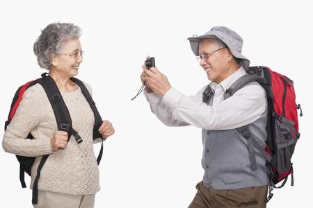 年配の男性がデジタル カメラで妻の写真を撮る 写真素材
