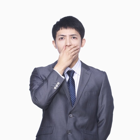 covering mouth: Businessman covering mouth with hand