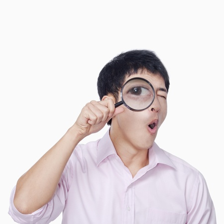 Young man looking through magnifying glass photo
