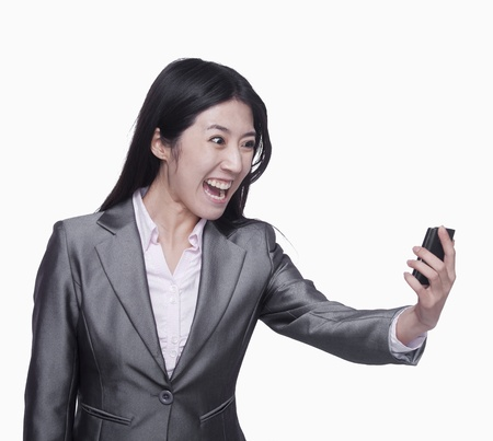 yelling: Businesswoman yelling at mobile phone