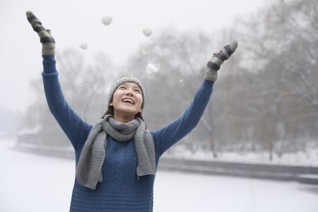 雪で遊ぶ若い女性 写真素材