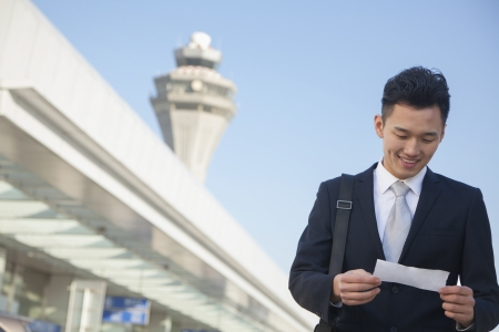Traveler looking at ticket at airport