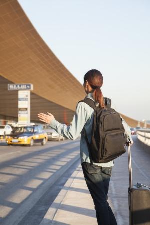 hailing: Young traveler hailing a taxi at airport