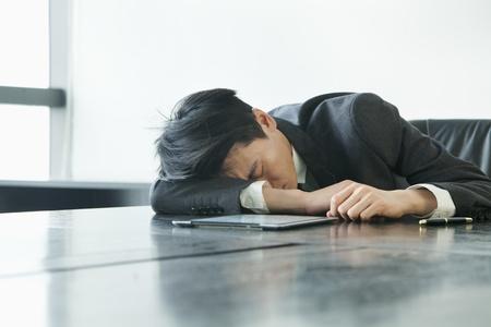 sleeping tablets: Businessman sleeping in office room Stock Photo