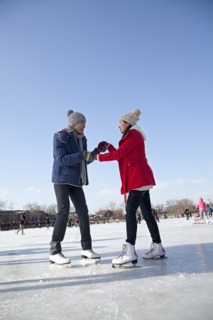 ice rink: Young couple skating at ice rink