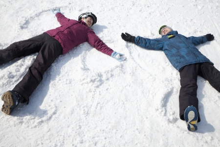 男と女の雪の天使を作る雪の上に横たわる