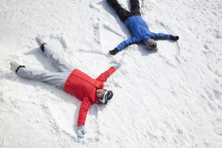 getting away from it all: Couple Lying On Snow Making Snow Angel Stock Photo