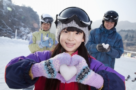 Family in Ski Resort, Daughter Showing Snow Heart