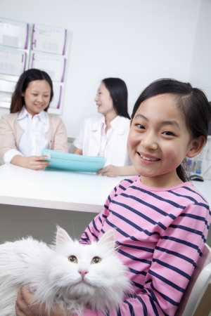 Woman and girl with pet dog in veterinarians office photo