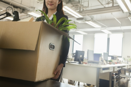 relocation: Young businesswoman moving box with office supplies
