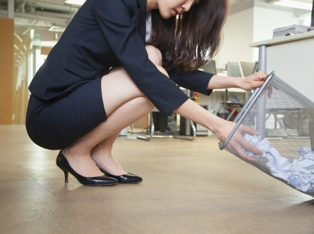wastepaper: Young businesswoman looking through wastepaper bin in office Stock Photo