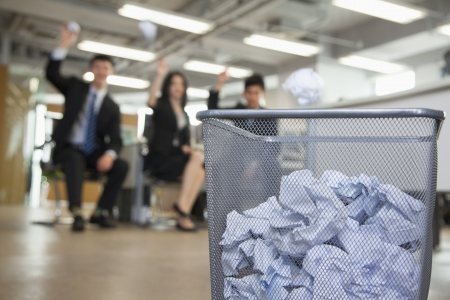 throw paper: Three coworkers preparing to throw paper into waste basket  Stock Photo