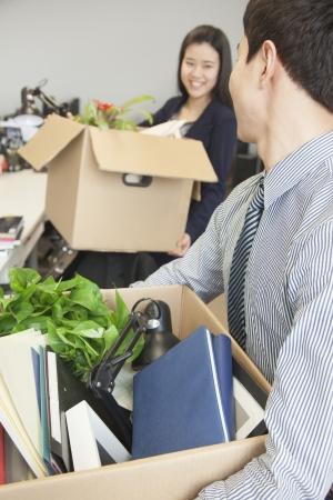 articulos de oficina: Dos j�venes empresarios que llevan las cajas con art�culos de oficina