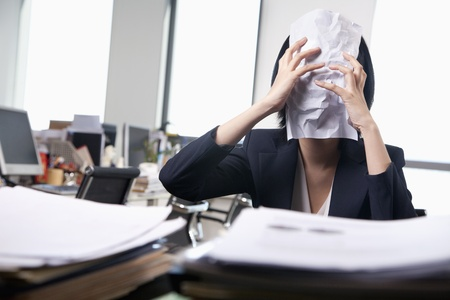obscured face: Young businesswoman sitting at desk covering her face with a paper