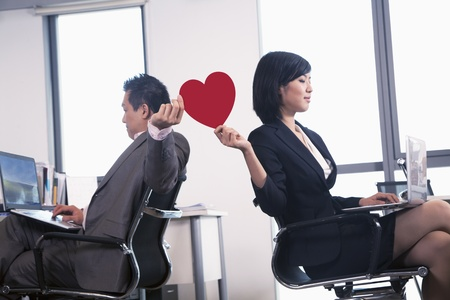 romance: Work romance between two business people holding a heart