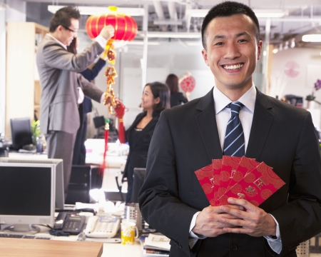 Businessman holding red envelopes and coworkers hanging decorations for Chinese new year photo