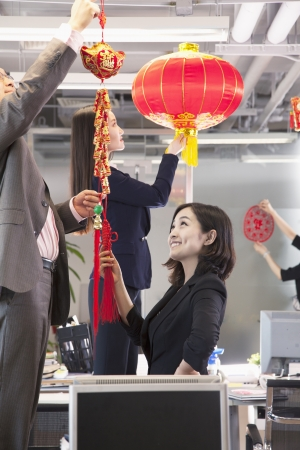 Coworkers hanging decorations in office for Chinese new year Stock Photo