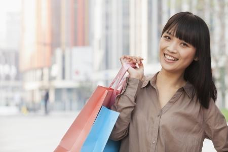 Portrait of young women holding shopping bags outdoors, Beijing photo