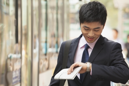 Young Businessman checking the time, waiting for the bus