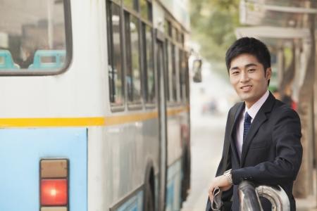 parada de autobus: Joven empresario de espera en la parada de autob�s para el autob�s Foto de archivo