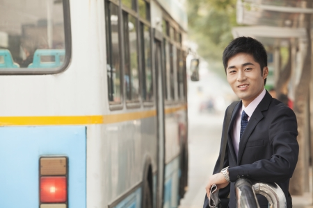 bus stop: Young businessman waiting at the bus stop for the bus