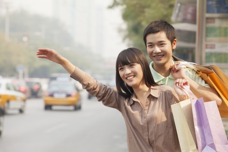 Young couple with shopping bags hailing a taxicab in Beijing photo