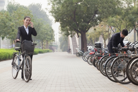 Young Business people parking their bikes and talking on the phone in Beijing photo