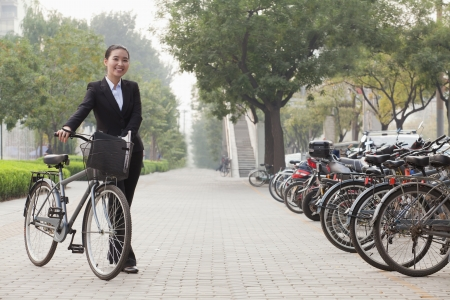 Young businesswoman holding a bicycle, sidewalk, Beijing photo