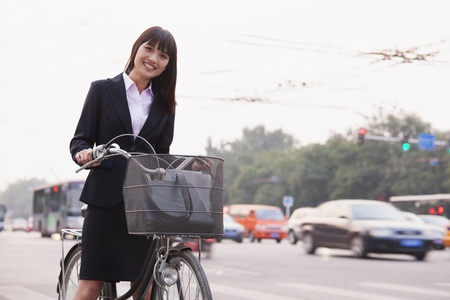 Young businesswoman riding a bicycle on the street, Beijing  photo