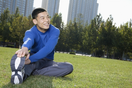 touching toes: Young Athletic Man Stretching in Beijing Park- Horizontal