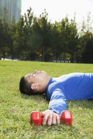 man lying down: Young Athletic Man Lying Down in Park with Dumbbells, Vertical Stock Photo