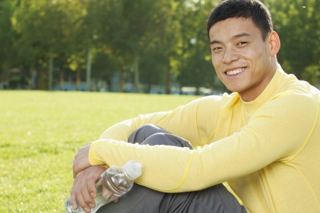 hugging knees: Young Athletic Man Sitting on the Grass in a Park