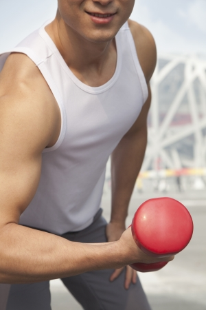 Young man exercising with dumbbell, close-up, midsection