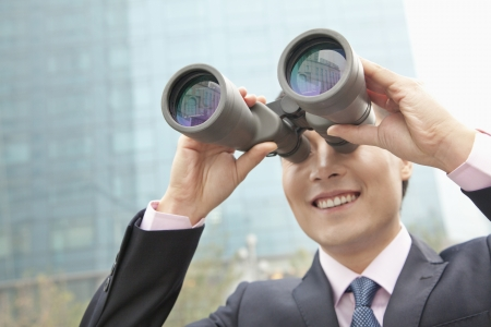 looking through an object: Smiling Businessman Using Binoculars, Reflection Stock Photo