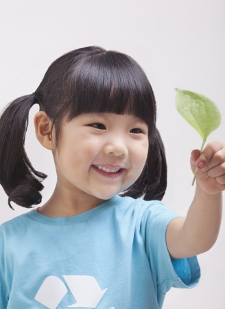 environmental issues: Little girl looking at leaf, close up studio shot Stock Photo