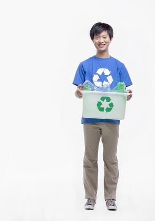 recycling bin: Portrait of young man holding recycling bin, studio shot
