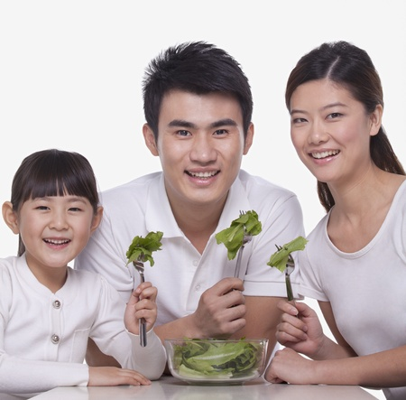 Family sharing a salad, studio shot photo