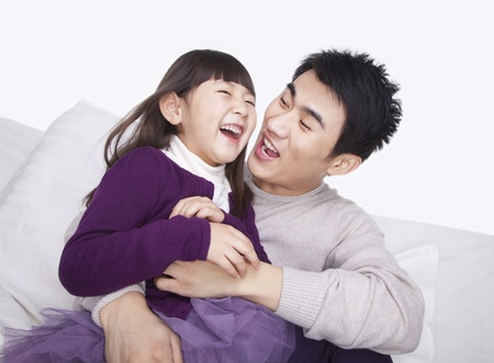 tickling: Father tickling daughter on the sofa, studio shot Stock Photo