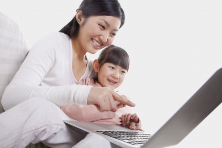 tilt: Mother and daughter sitting on sofa using a laptop, tilt Stock Photo