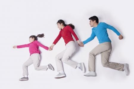 imitating: Family holding hands and imitating running, studio shot
