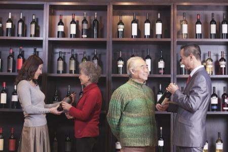 wine store: Four People Examining Wine at a Wine Store