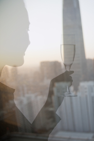 champagne flute: Double exposure of woman toasting with champagne flute over cityscape