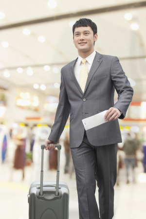 incidental people: Young business man walking with suitcase and holding flight ticket in airport
