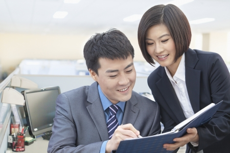 Two Business People Looking at Note Pad photo