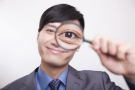 Young businessman looking through magnifying glass, studio shot photo