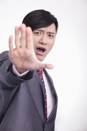 stop gesture: Young businessman with hand raised in stop gesture, studio shot