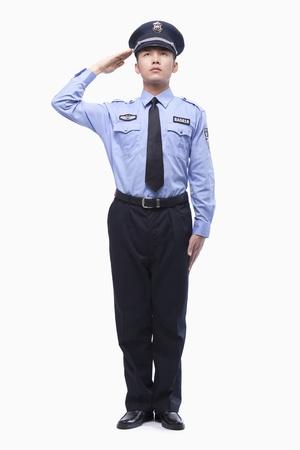 policier: Policier Faire le salut militaire, Prise de vue en studio, pleine longueur Banque d'images
